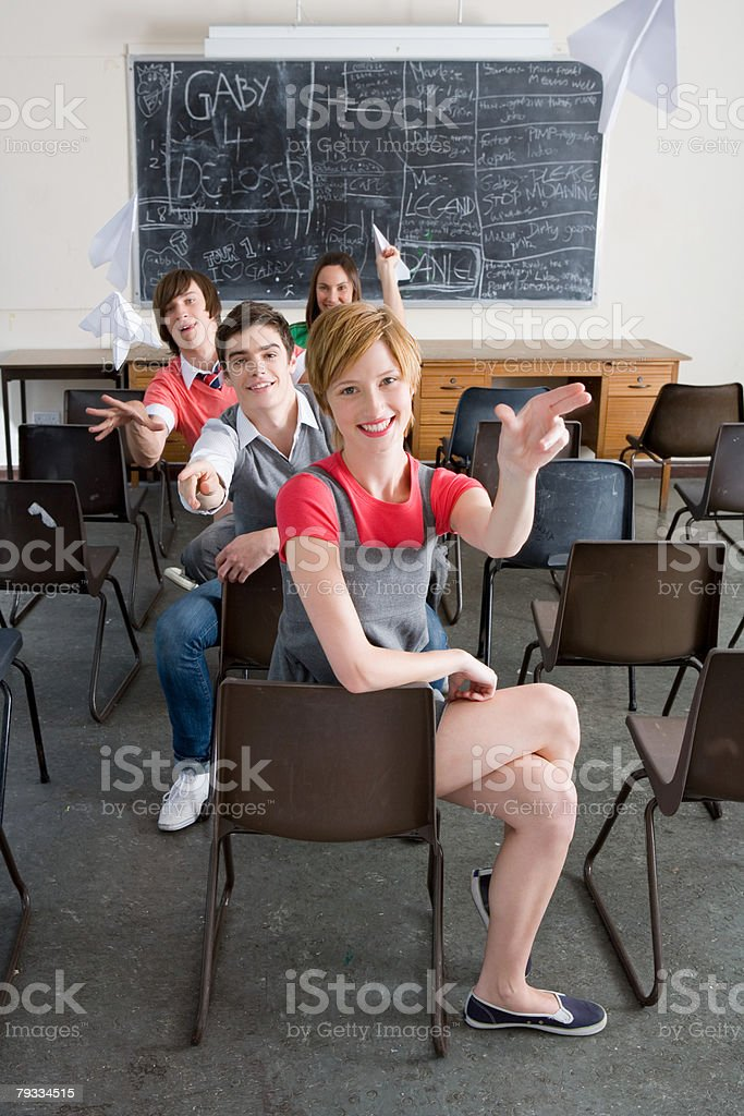 Teenagers throwing paper aeroplanes royalty-free stock photo