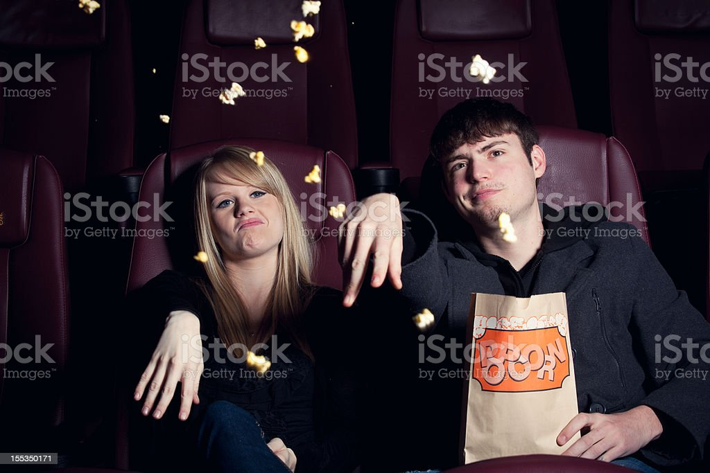 Teenagers Throwing Popcorn at the Movie Screen stock photo