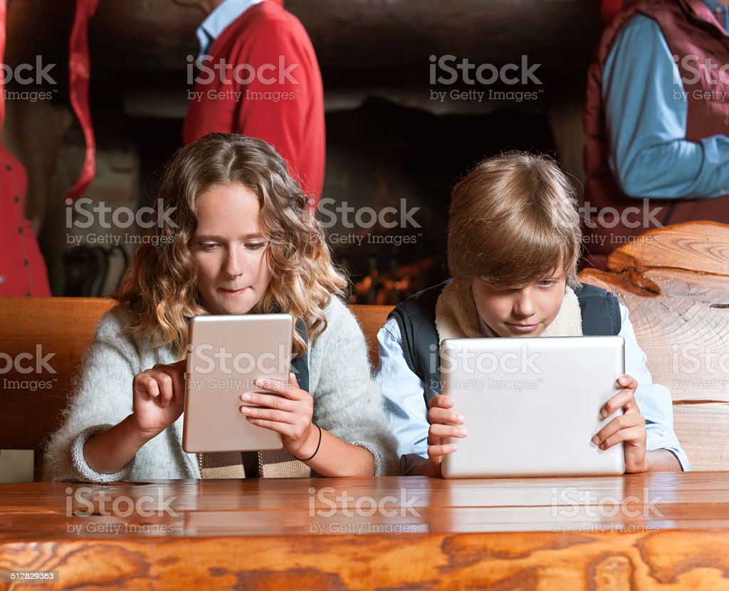 Teenagers with digital tablets Girl and boy sitting at the table and using digital tablets with adults standing by fireplace in the background. 12-13 Years Stock Photo