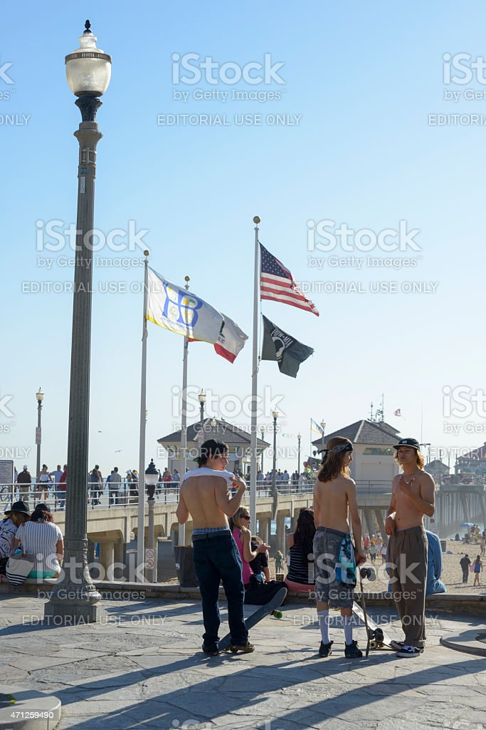 Teenagers With Skateboards At Huntington Beach Pier In Orange Co