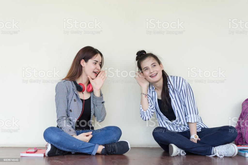 Teenagers women gossip girlfriend sharing secrets smiling sitting talking surprise in the ear, copy space background stock photo