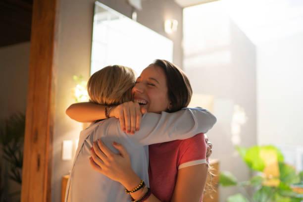 teenagr girl and mature woman embracing - abbracciare una persona foto e immagini stock