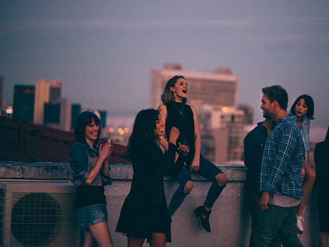 Group of multi-ethnic teenager friends celebrating a funny rooftop party