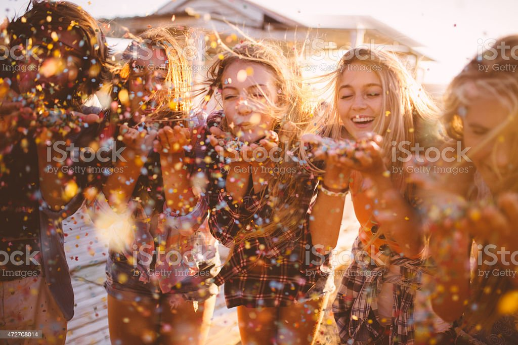 Teens celebrating with colourful confetti outside on summer evening stock photo