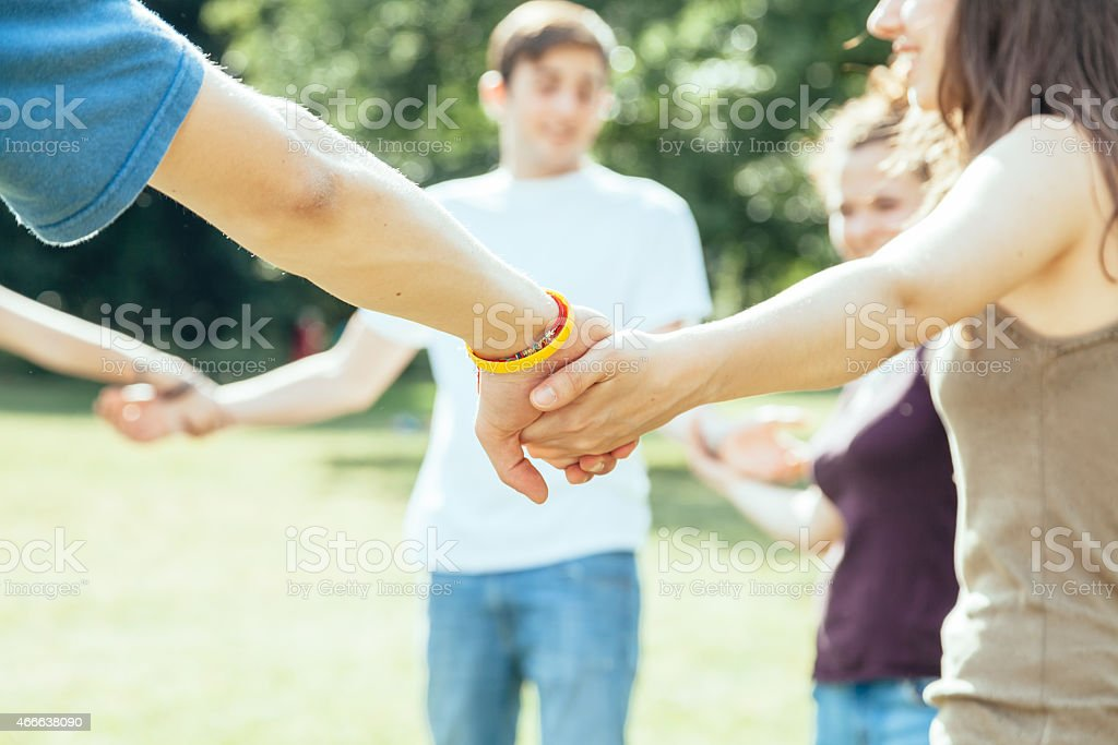 Teens forming circle holding hands outside on green grass stock photo