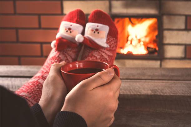 teenie hände halten eine rote tasse kaffee vor dem kamin. weihnachtsfeiertage. - frohes neues jahr stock-fotos und bilder