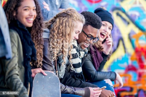 A group of teenagers are sitting in front of a wall covered in graffiti. They are wearing stylish clothes. Everyone is enjoying spending time together.