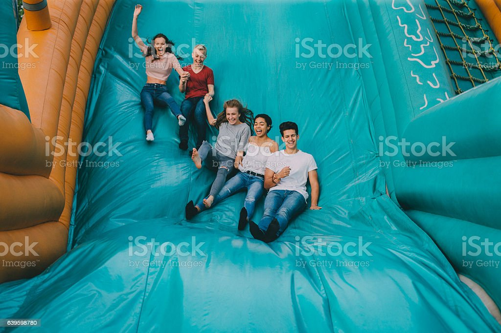 Teens Jumping Down Slide stock photo