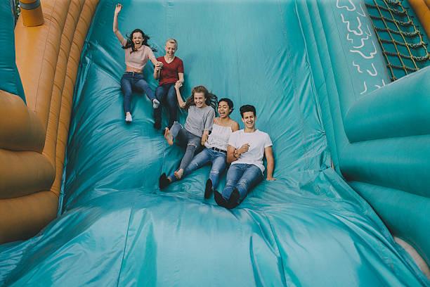 Teens Jumping Down Slide stock photo