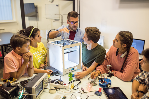 Group of students, working on some robot project at electronic course, they working with 3D printer on robo arm. Working table full of different oscilloscopes and equpment needed for recording electrical circuits, 3D printer there too.Instructor helping children with project