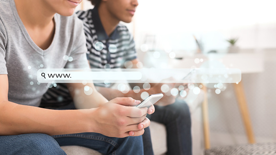 921148564 istock photo Teens surfing online on smartphone with virtual blank search bar 1083603084
