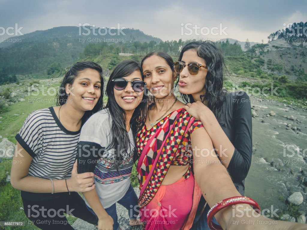 Teens taking selfie with family in hills. stock photo