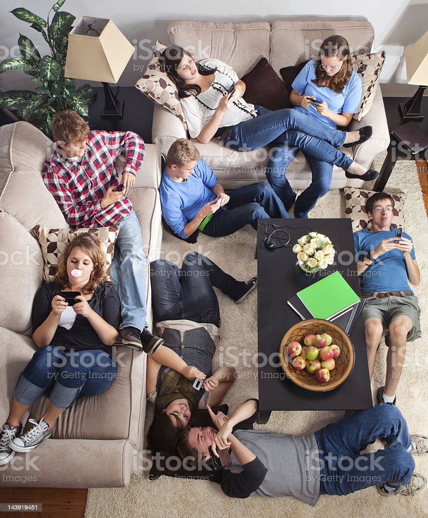 Teens texting in a living room stock photo