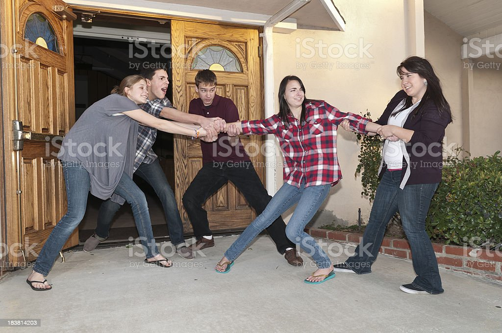 Teens Trying to Pull Another into Church stock photo