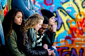 A group of teenagers are sitting in front of a wall covered in graffiti. They are wearing stylish clothes. A boy and girl are looking at a smartphone screen together.