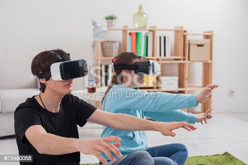 Virtual reality. Teens with virtual glasses are playing in the living room