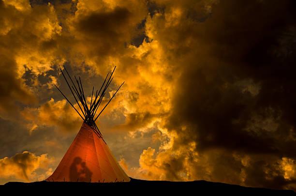 indianerzelt und gold sunset- licht und menschen im tipi - indianer tipi stock-fotos und bilder