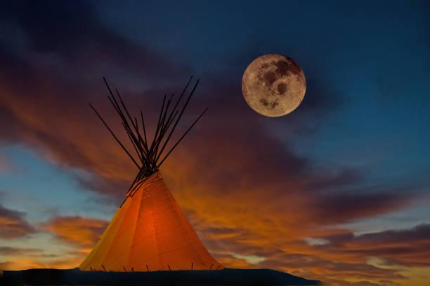 tipi bei sonnenuntergang mit vollmond - indianer tipi stock-fotos und bilder