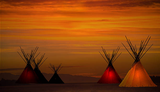 Teepee camp and gold, dark,  sunset- light in teepees stock photo