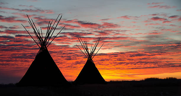 teepee camp and gold, dark,  sunset- two - indianer tipi stock-fotos und bilder