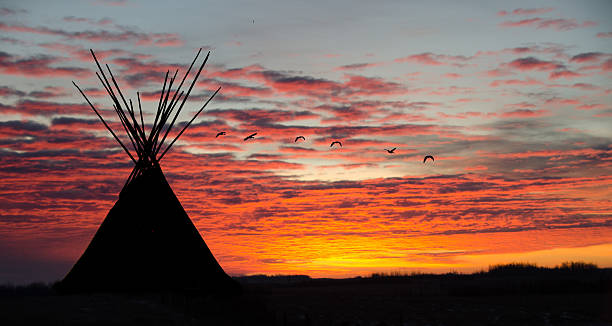 teepee camp and orange sunrise with small flock of geese - indianer tipi stock-fotos und bilder