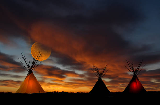 Teepee camp at sunset with full moon A prairie First Nation teepee cam at sunset. Full moon indigenous peoples of the americas stock pictures, royalty-free photos & images