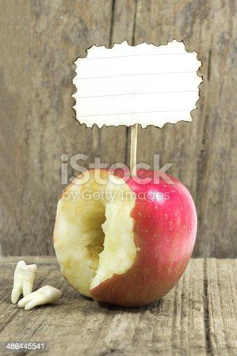104545719istockphoto teeth against red apple 486445541