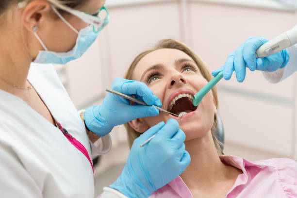 Teeth care Horizontal color close-up headshot of beautiful woman having dental examination. suction tube stock pictures, royalty-free photos & images
