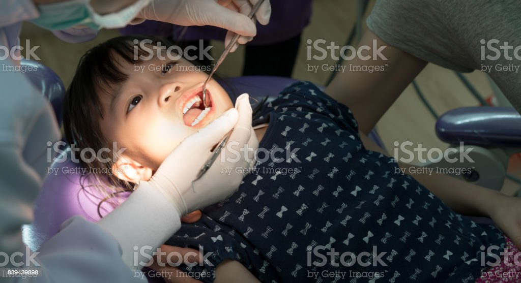 Teeth checkup at dentist's office. Dentist examining Asian girls teeth stock photo