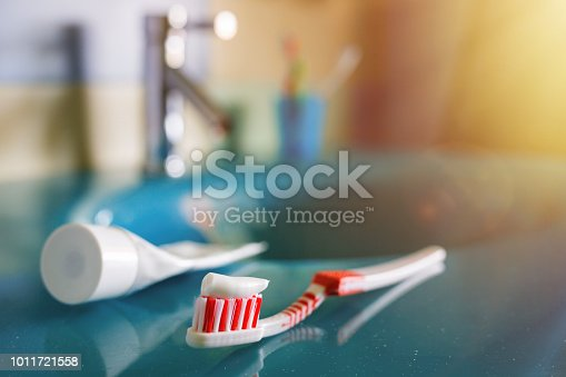 teeth health: brush and toothpaste on blue sink in bathroom. red toothbrush lies in the interior on background of water tap.