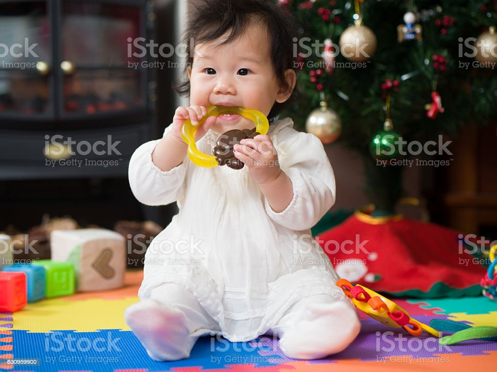 Teething baby girl playing with teething toy stock photo