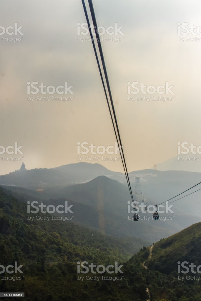 Tele zoom view of Giant Tian Tan Buddha statue on the peak of the mountain, view from Ngong Ping 360 cable car at Po Lin Monastery in Lantau Island, Hong Kong stock photo