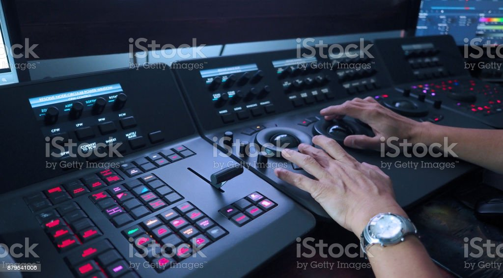 Telecine controller machine and man hand editing or adjusting color stock photo
