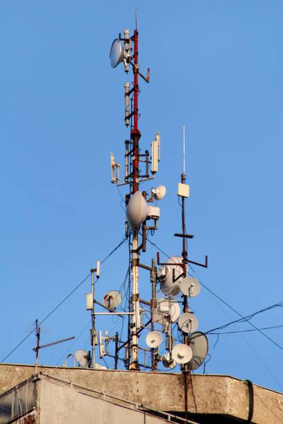 Base de telecomunicações estações repetidoras da rede no telhado do edifício. A comunicação celular antena no telhado de construção da cidade. Torre de telecomunicações de telefonia celular. Antenas no topo do edifício. - foto de acervo