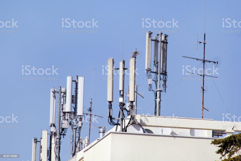 Estações base de telecomunicações rede repetidores no telhado do edifício. A comunicação celular aérea em um telhado do prédio. Torre de telecomunicações de telefonia celular. Antenas no topo do edifício. - foto de acervo