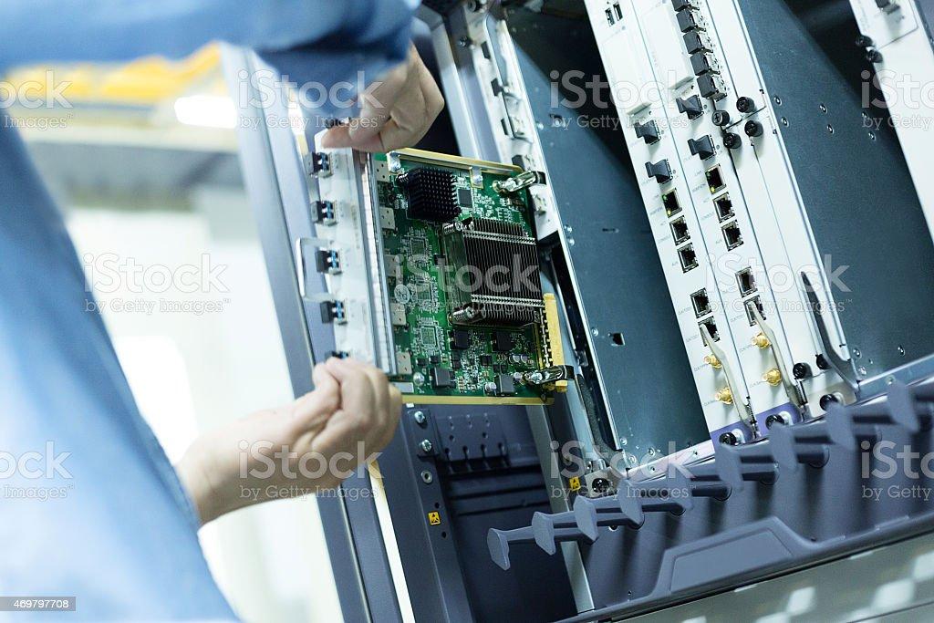 telecommunication engineer install hardware to the data server - Royalty-free 2015 Stock Photo