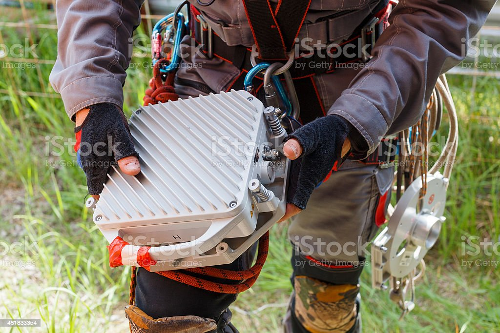 telecommunication equipment in the hands of the climber stock photo