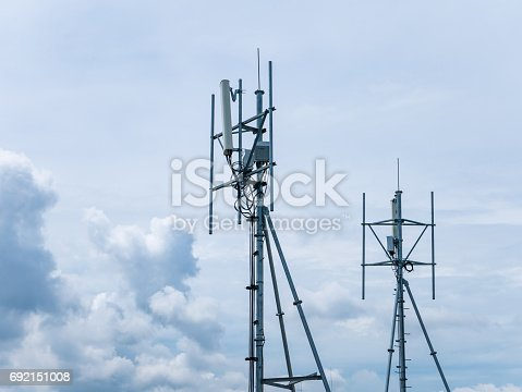 istock Telecommunication GSM (4G) tower (antenna, transmitter), blue sky, white clouds 692151008