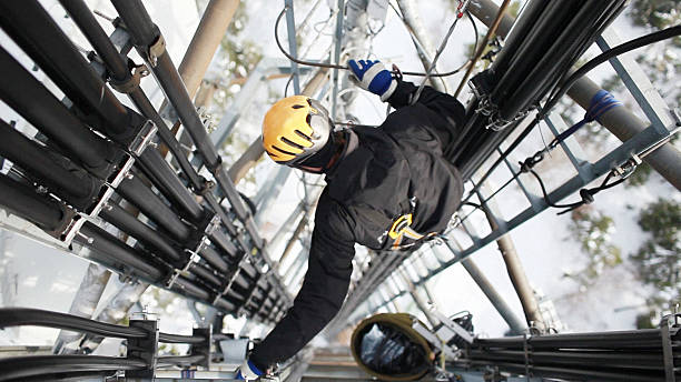 telecommunication manual high worker engineer repairing antenna - high up stock photos and pictures