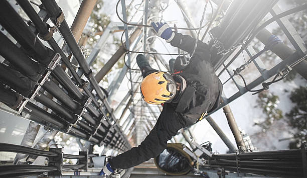 Telecommunication manual high worker engineer repairing antenna Telecommunication manual high worker engineer repairing 260 feet tall mobile base station (communication tower), high angle of view.  power occupation stock pictures, royalty-free photos & images