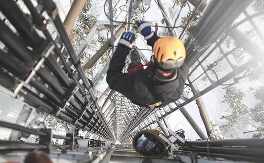 Telecommunication manual high worker engineer repairing 260 feet tall mobile base station (communication tower), high angle of view.
