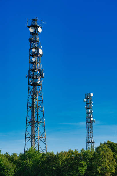 telecommunication masts TV antennas wireless technology against blue cloudless sky over green hedges stock photo