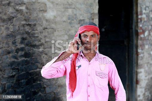 Rural men talking on mobile phone portrait outdoor.