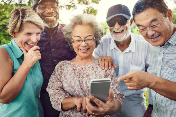 telecommunication technology togetherness concept - elderly group stock photos and pictures