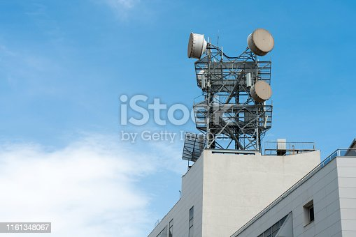 istock Telecommunication, telephone pole or communication tower with antennas on the top of building outdoor on beautiful blue sky. 1161348067