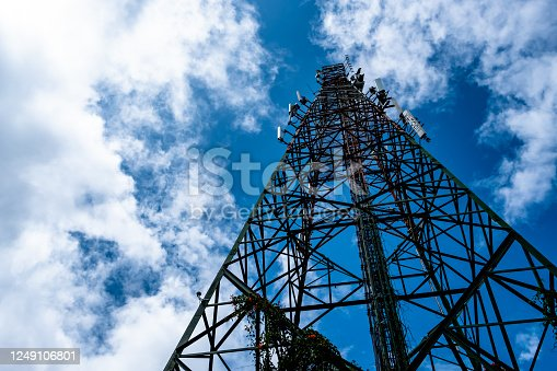 Telecommunication tower against blue sky with scattered cumulus white clouds. Worm's eye view.