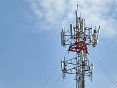 LTE, GSM, 2G, 3G, 4G, 5G tower of cellular communication. Telecommunication tower against the blue sky with clouds.