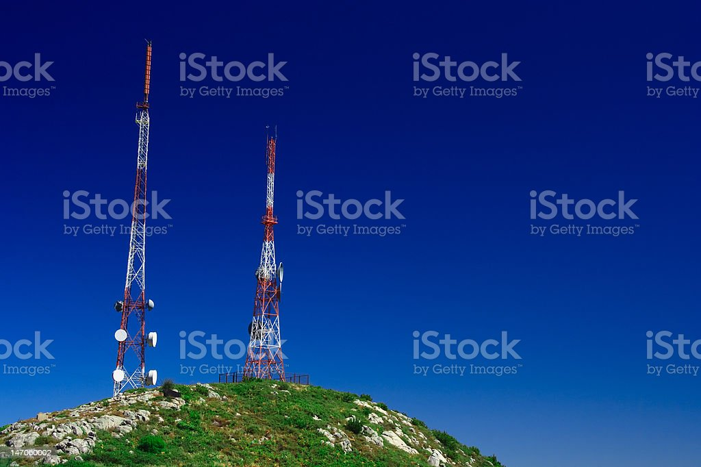 Telecommunication tower on the green field with blue sky royalty-free stock photo