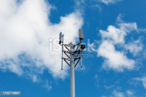 Telecommunication tower with 4G, 5G transmitters. Cellular base station with transmitter antennas on a telecommunication tower on against a blue sky with clouds.