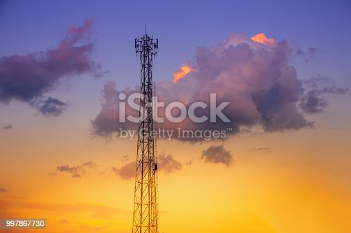 istock Telecommunication tower with antenna and technician working on sunset sky 997867730